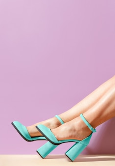 パステルパープルの背景に美しい女性の脚にスタイリッシュな青いスエードのハイヒールの靴。