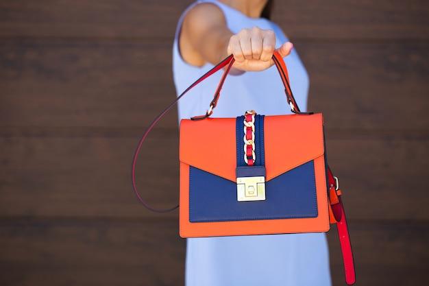 Стильная синяя кожаная женская сумка оранжевого цвета. девушка держит в руке. сумка крупным планом. крупный план.
