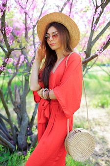 Stylish bohemian girl posing in coral dress and straw hat near blossom cherry tree in spring park.