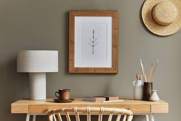 木の机、籐の肘掛け椅子、茶色の枠、帽子、事務用品、ランプ、装飾、家の装飾にエレガントなパーソナル アクセサリーを備えた、スタイリッシュなボヘミアン インテリア