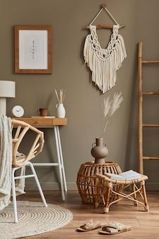 木の机、籐の肘掛け椅子、茶色の枠、マクラメ、事務用品、ランプ、装飾、家の装飾にエレガントなパーソナル アクセサリーを備えた、スタイリッシュなボヘミアン インテリアのホーム オフィス スペース。