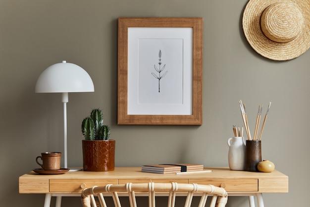 木製の机、籐のアームチェア、茶色のポスターフレーム、サボテン、事務用品、帽子、装飾、家の装飾のエレガントなパーソナルアクセサリーを備えたホームオフィススペースのスタイリッシュなボヘミアンインテリア