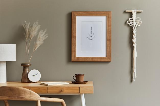 木製デスク籐アームチェアブラウンポスターフレームマクラメ事務用品ランプ装飾と家の装飾のエレガントなパーソナルアクセサリーとホームオフィススペースのスタイリッシュなボヘミアンインテリア