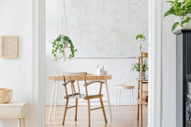 Stylish boho home interior of  workspace with wooden desk chair lamp and white shelf design and elegant personal accessories
