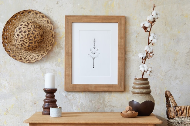 Stylish boho interior of living room with brown mock up poster frame, elegant accessories, flowers in vase, wooden shelf and hanging rattan hut. minimalistic concept of home decor. template.