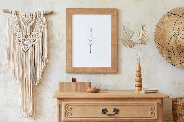 茶色のフレーム、エレガントなアクセサリー、花瓶に花、木の棚、吊り下げられた籐の小屋を備えた、スタイリッシュで自由奔放に生きるリビング ルームのインテリア。家の装飾のミニマルなコンセプト..