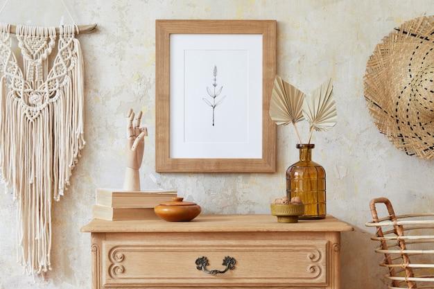 茶色のモックアップポスターフレーム、エレガントなアクセサリー、花瓶の花、マクラメ、ぶら下がっている籐小屋のあるリビングルームのスタイリッシュな自由奔放に生きるインテリア。家の装飾のミニマルなコンセプト。テンプレート。