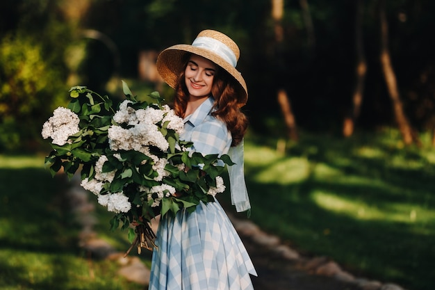 Stylish boho woman in hat posing at lilac flowers in sunny spring park. calm portrait of beautiful hipster girl standing in purple lilac bush in spring garden.