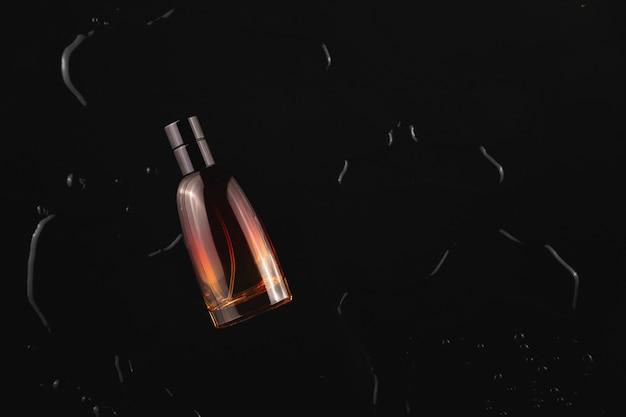 光の中でキラキラ光る水滴の中で黒い背景にメンズ香水のスタイリッシュなボトルトップビューコピースペース