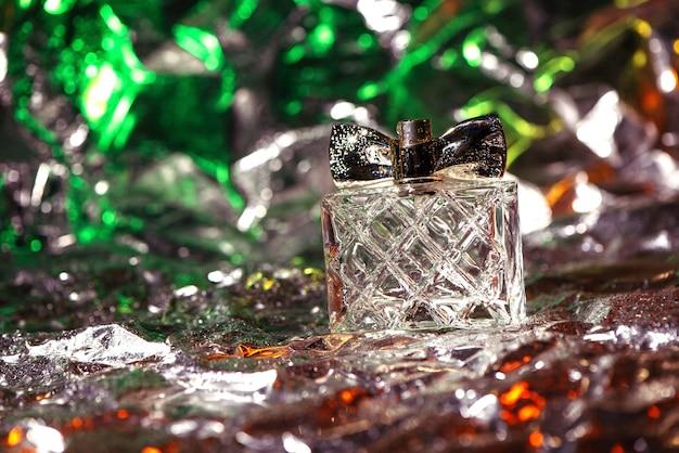 女性の香水のスタイリッシュなボトルは、光沢のあるしわくちゃの表面を持つホイルの緑、赤、銀のネオンライトでクローズアップ Premium写真