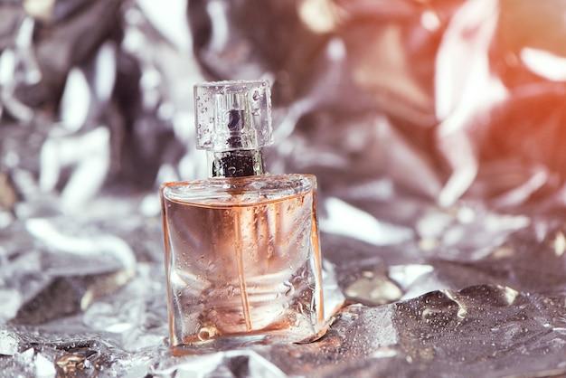光沢のあるしわくちゃの表面の銀と水滴が付いているホイルの上の女性の香水のスタイリッシュなボトル