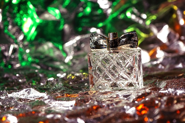 Stylish bottle of women perfume close up in green, red and silver neon lights on the foil with shiny crumpled surface
