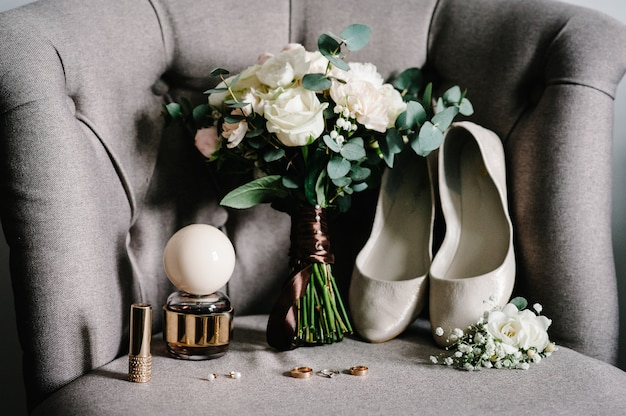 レトロなアームチェア、結婚式のアクセサリーの花嫁の花のスタイリッシュな花束:花、ボタンホール、靴、香水、口紅、イヤリング、素朴な背景の金の結婚指輪。休日のコンセプト。
