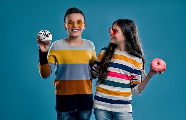 マルチカラーのセーターとドーナツが青に分離された色のメガネのスタイリッシュな男の子と女の子。