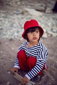 夏の海沿いの小石のビーチにベストのスタイリッシュな男の子の子供が座っています