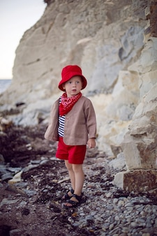 夏の海沿いの小石のビーチにベストを着たスタイリッシュな男の子の子供が立っています