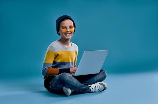 스트라이프 컬러 스웨터, 모자 및 노란색 안경을 입은 세련된 소년은 다리를 꼬고 앉아서 공부하거나 파란색에 고립 된 노트북에서 게임을합니다.