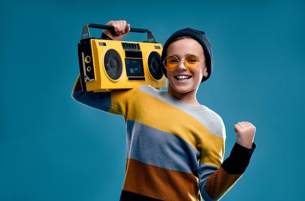 Стильный мальчик, одетый в полосатый свитер, шляпу и желтые очки, держит ретро магнитофон, изолированный на синем фоне.