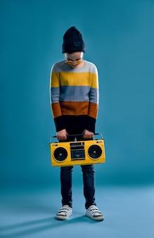 줄무늬 스웨터, 모자와 노란색 안경을 입은 세련된 소년은 파란색에 고립 된 복고풍 테이프 레코더를 보유하고 있습니다.
