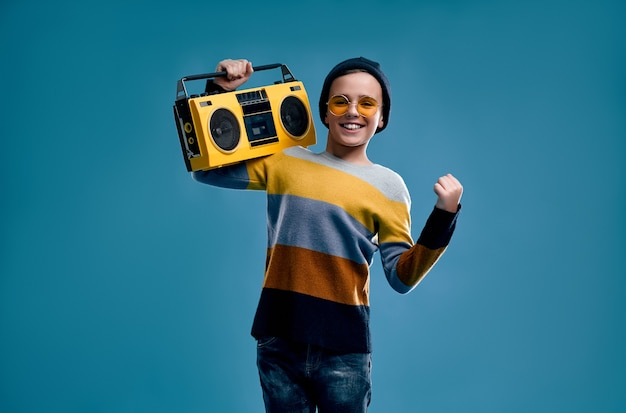 Stylish boy dressed in a striped sweater, hat and yellow glasses holds a retro tape recorder isolated on a blue.