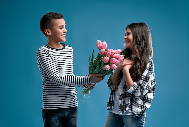 Stylish boy gives a bouquet of tulips flowers to a cute little girl isolated on a blue. love concept.