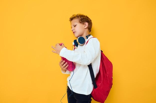 헤드폰 물병 노란색 배경에 세련 된 소년입니다. 고품질 사진