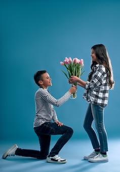 スタイリッシュな男の子がひざまずいて、かわいい女の子にチューリップの花の花束を与えます