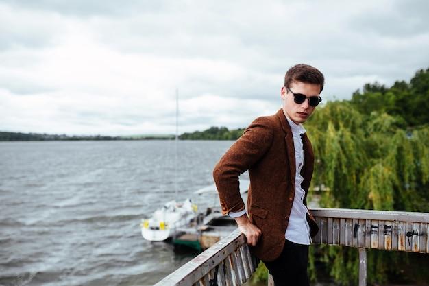 Stylish boy posing with lake background