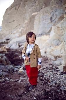 夏にはベストと赤いズボンを着たスタイリッシュな男の子の船乗りが海岸に立っています