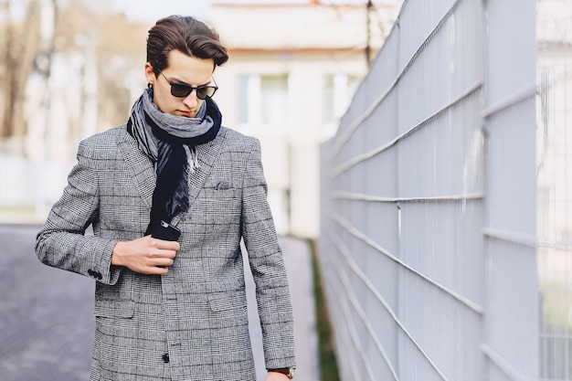 Stylish boy in sunglasses in coat with briefcase on street