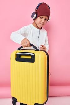 ヘッドフォンエンターテイメントを身に着けている黄色のスーツケースを持つスタイリッシュな男の子