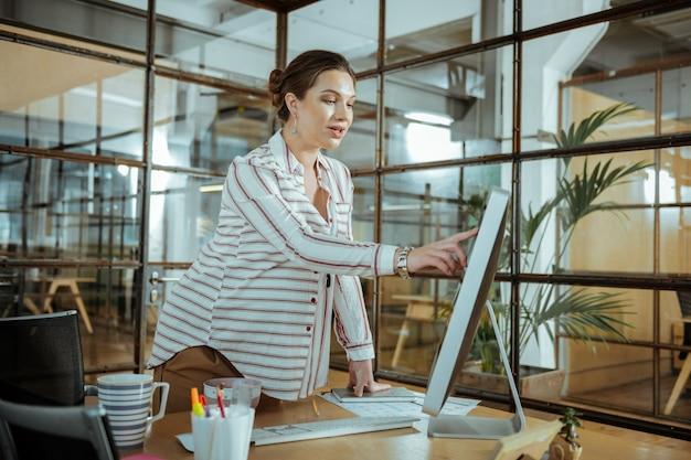 Стильный браслет. беременная бизнесвумен в стильном браслете работает возле компьютера