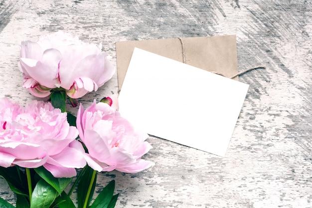 アートワークを表示するスタイリッシュなブランディングモックアップ。空白のグリーティングカードまたはピンクの牡丹の花の結婚式の招待状