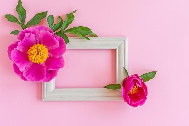 デザインを表示するスタイリッシュなブランディングモックアップ。フォトフレームと咲く牡丹の花で作られたパステルピンクの背景にモックアップ。フラットレイトップビュー。