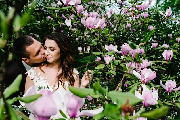 Стильная невеста и жених позируют с деревом магнолии с розовыми цветами.