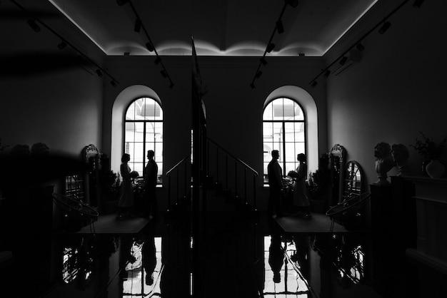 세련된 신부와 신랑은 거울에 나란히 앉아 흑백 사진을 찍는다