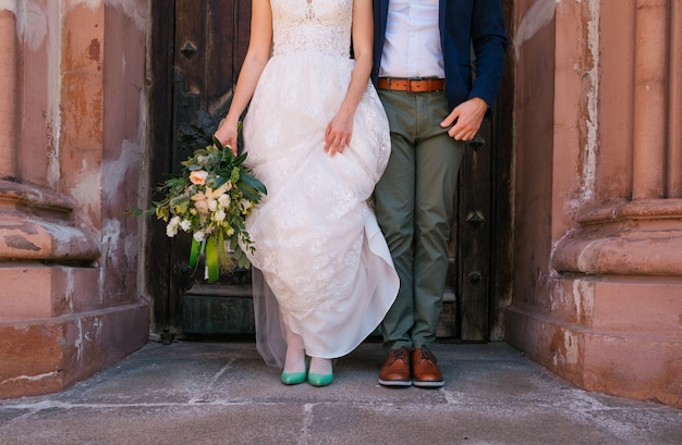Stylish bride and groom stand at the door