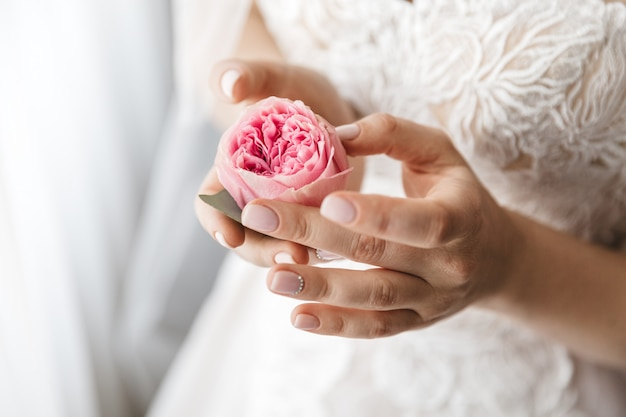 Stylish bride holds a rose