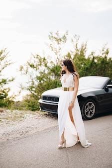 Стильная невеста в солнцезащитных очках стоит возле черного кабриолета на дороге в горах