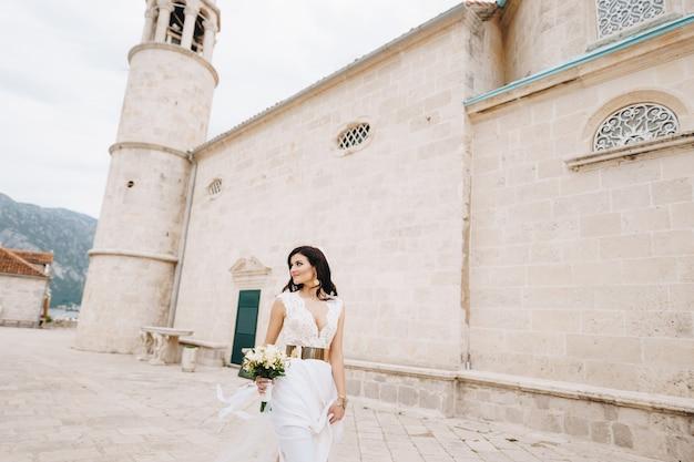 Стильная невеста стоит у стен древней церкви скал богоматери в которском заливе.