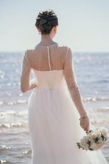 A stylish bride stands with her back beautiful wedding bouquet in the hands of the bride beautiful a...