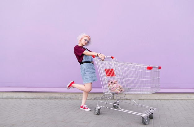 Stylish bright girl with colored hair poses with a shopping cart on a purple background