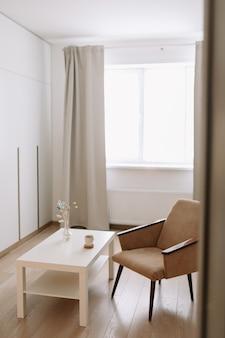 창가에 편안한 안락 의자와 테이블이있는 세련되고 밝은 거실.