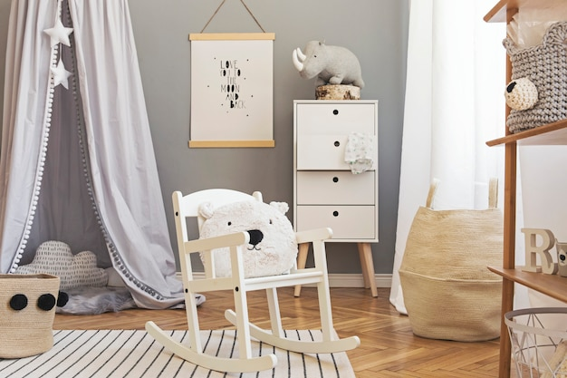 Stylish and bright scandinavian decor of newborn baby room with mock up poster, white design furnitures, natural toys, hanging grey canopy with wooden cradle, bookstand, accessories and teddy bears.