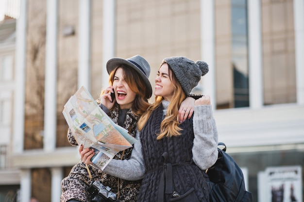 Stylish brightful image of amazing excited joyful women travelling with citymap, backpack in sunny city. expressing positivity, lovely moments, best friends together, fashionable look.