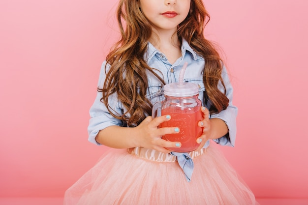Stylish brightful image of cute little girl with long brunette hair, in tulle skirt holding glass with juice isolated on pink background. happy childhood with lovely drink, tasty young years