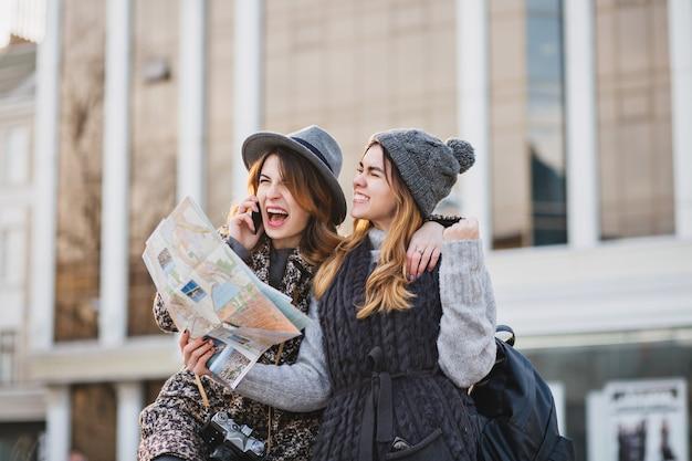 Стильное яркое изображение удивительных возбужденных радостных женщин, путешествующих с картой города, рюкзаком в солнечном городе. выражение позитива, прекрасных моментов, лучших друзей вместе, модного образа.