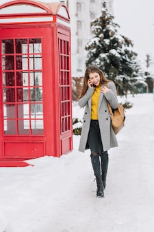 Stylish british image of fashionable young woman walking on street in winter time near red telephone box. talking on phone, true positive emotions, laughing, smiling.