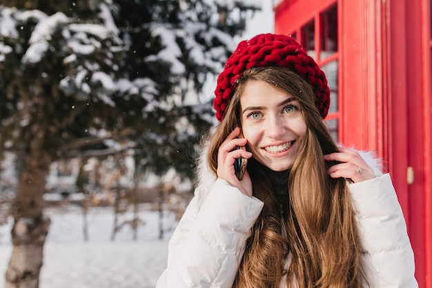 Stylish british portrait of amazing young woman with long brunette hair in red hat talking on phone on street full with snow. enjoying cold winter time, cheerful mood. place for text.