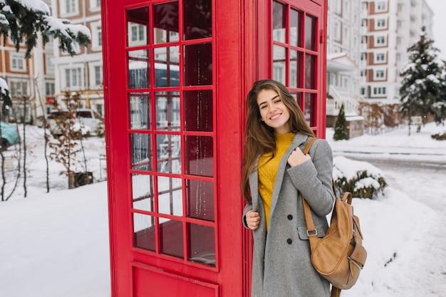 눈 가득한 거리에 빨간 전화 박스 근처 거리에 걷는 긴 갈색 머리를 가진 매력적인 젊은 여자의 세련 된 영국 초상화. 차가운 눈 날씨, 미소, 겨울 방학, 기쁨.